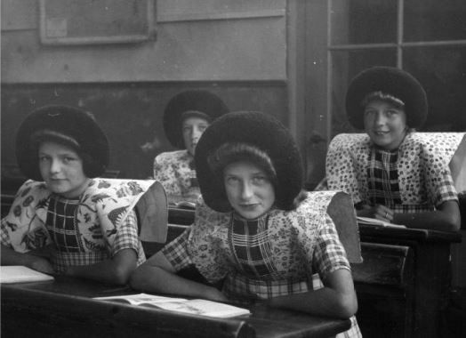 Groepsportret van enkele meisjes in klederdracht in de schoolbanken van een klaslokaal van de school te Eemdijk (gemeente Bunschoten). 1948 WF van Heemskerck Düker (fotograaf) #Utrecht #Spakenburg