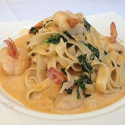 Pasta con camarones al chipotle 250g linguine or spaghetti Salt, to taste 1 tablespoon olive oil 2 cloves garlic, finely chopped 500 grams of shrimp, peeled and deveined 2 tablespoons tequila reposado (eg González Reserve ®) 1 cup fresh spinach 1 cup heavy cream 2 chipotle chiles in adobo, or to taste 1 teaspoon chicken bouillon powder Pepper, to taste 2 tablespoons freshly grated Parmesan cheese