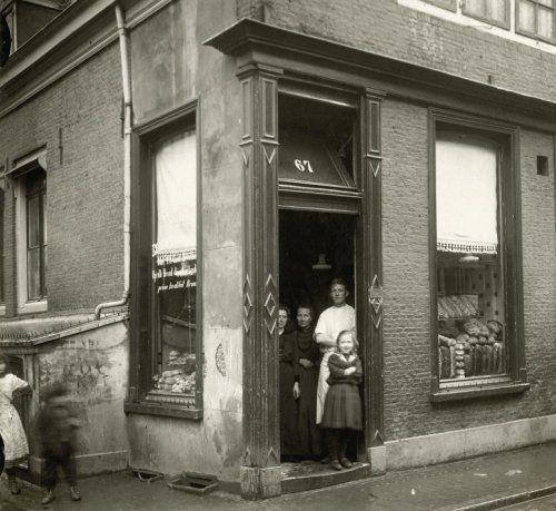 Buitenkant van broodwinkel / bakkerij in Amsterdam, met de bakker en zijn vrouw en kind in de deuropening. Nederland, 1916.