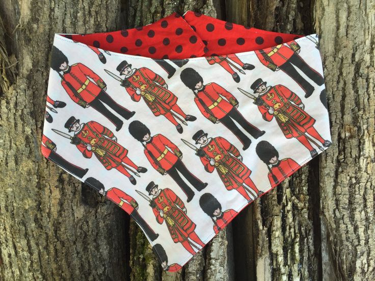 Pet Bandana made by Polka Dot Tails. Each bandana is made with 100% cotton.  The bandana has a contoured neck for a comfortable, well fitted size.    Material has been pre-washed to reduce shrinking.   Each bandana has been top stitched to ensure a lay flat fit.   ('London Calling soldiers' fabric design by Hazel Fisher Creations.)