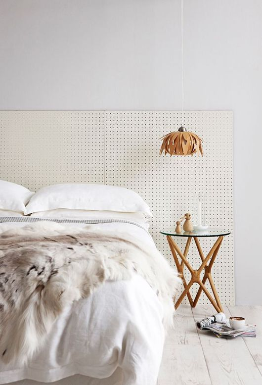 Perforated headboard - smart move made luxe with a fur through, style-savvy side table and hanging pendant.
