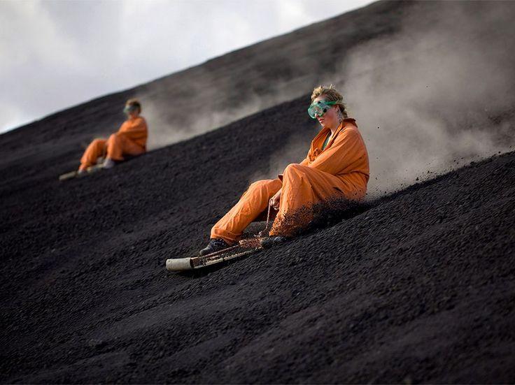 """Adecuado en el equipo de protección, los turistas """"ash board"""" abajo del volcán Cerro Negro de Nicaragua. La actividad es un punto culminante de una gira de viajes de aventura que visita el volcán, el más joven de América Central"""