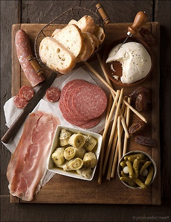 Antipasto: Prosciutto, salami, marinated peppers and artichokes, olive assortment, loaves of fresh bread, cheeses, nuts, etc..