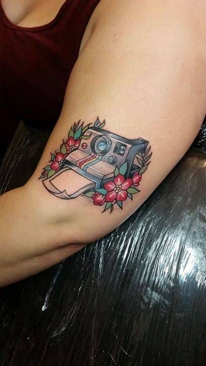 Kawaii style polaroid camera tattoo on the left upper arm.