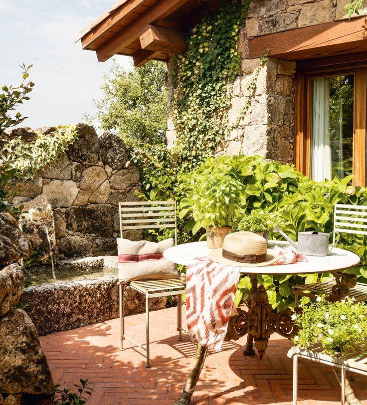 Junto a la fuente. Mesa de hierro y mármol y sillas de Becara. Cojín de lino de Mmimmo.
