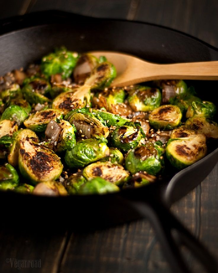 2 Tbsp olive oil 3 cups fresh Brussels sprouts, sliced in half 1 onion, chopped 2 Tbsp sesame seeds 1/2 tsp coarse sea salt