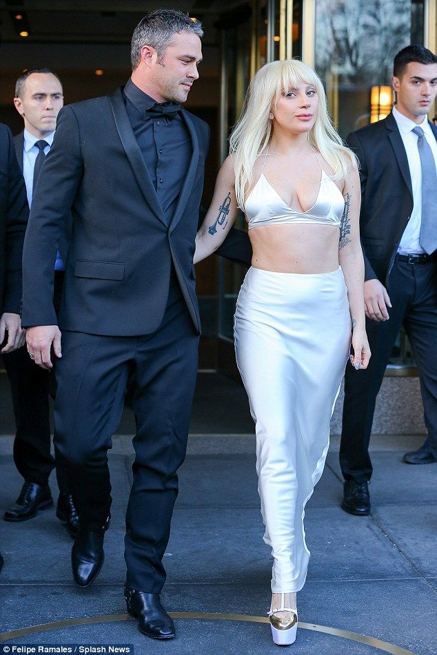 Flawless: Lady Gaga wowed in all-white satin two-piece set, revealing her toned body while heading to Billboard's 10th Annual Women in Music luncheon with her fiancé, Taylor Kinney, in New York City on Friday