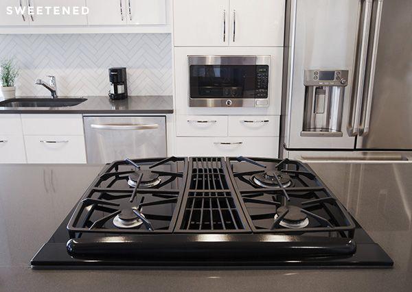 sleek midtown kitchen features jennair downdraft stove stainless steel ge fridge ge microwave