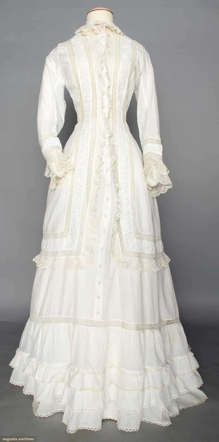 "WHITE COTTON MORNING DRESS, 1870s 1-piece, princess lines, trimmed w/ cream bobbin lace, low bustle back, CF thread-covered buttons, side pockets, trained & ruffled skirt, B 32"", W 25"", CF L 57"", CB L 70"","