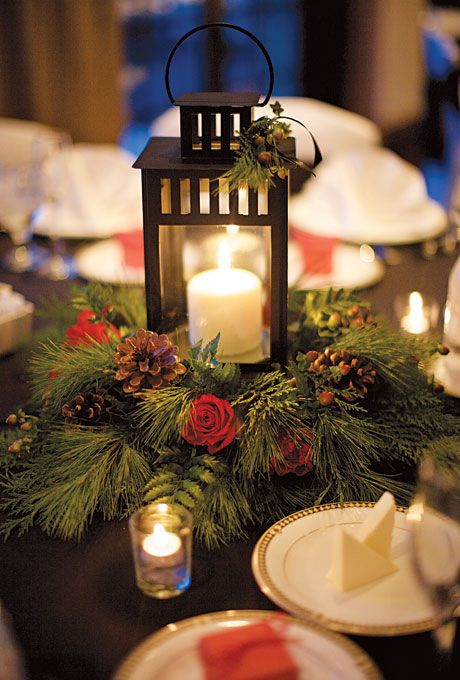 Brides.com: Winter Wedding Flowers. Wedding centerpiece of lanterns, pine boughs, roses, and pinecones by Grapevine Floral Company  Browse more winter wedding centerpieces.
