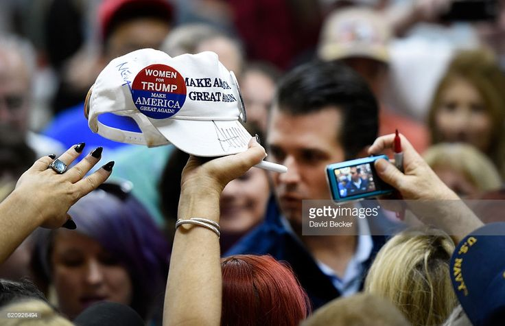 A women raises a ball cap in support for Republican presidential nominee Donald Trump to be signed by his son, Donald Trump Jr. at a get-out-the-vote rally at Ahern Manufacturing on November 3, 2016 in Las Vegas, Nevada. Trump Jr. urged people to vote for his father during early voting, which ends on November 4 in the battleground state, and on Election Day November 8.