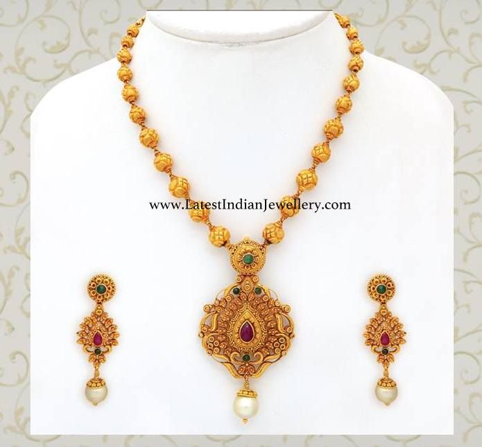 Beautiful gold haram with gold balls chain attached to intricately worked antique gold pendant and paired with gold long earrings