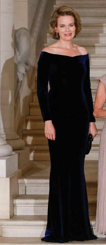 Reina Matilde de Bélgica   Acto: Gala con el Gobernador General de Canadá y su esposa, Bruselas (Bélgica).   Fecha: 27 de octubre de 2014.   'Look': La reina Matilde lució un vestido largo en terciopelo azul noche que dejaba sus hombros al descubierto. Completó el diseño con un 'clutch', en negro.