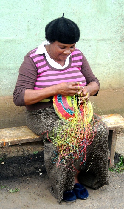 Artisan weaving a large bowl from industrial telephone wire.