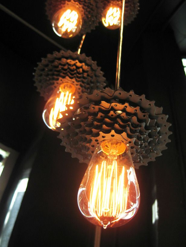 Industrial Chic  Repurposed bicycle gear sets are transformed into a multipoint pendant fixture using Edison-style filament bulbs. Would be great hanging above reception desk.