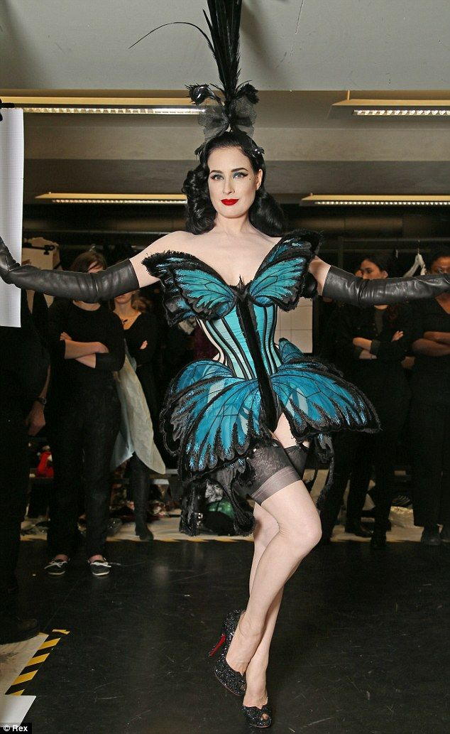 French fashion designer Jean-Paul Gaultier, right, unveils burlesque artist Dita Von Teese, wearing one of Gaultier's butterfly showgirl-inspired creations. (January 2014)