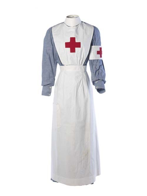 c.1914-18  First World War volunteer nurse's uniform: The uniform comprises a blue cotton chambray dress with concealed buttons down the centre front & a starched white cotton apron & cap. The nurses caps in addition to covering hair, were used to denote rank or seniority. Museum of London