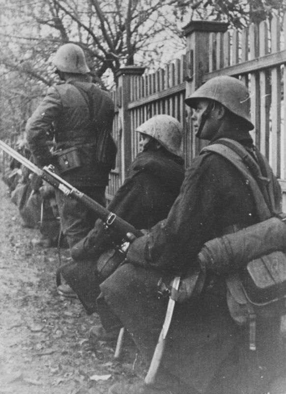 Romanian infantry near a fence in a Soviet village.