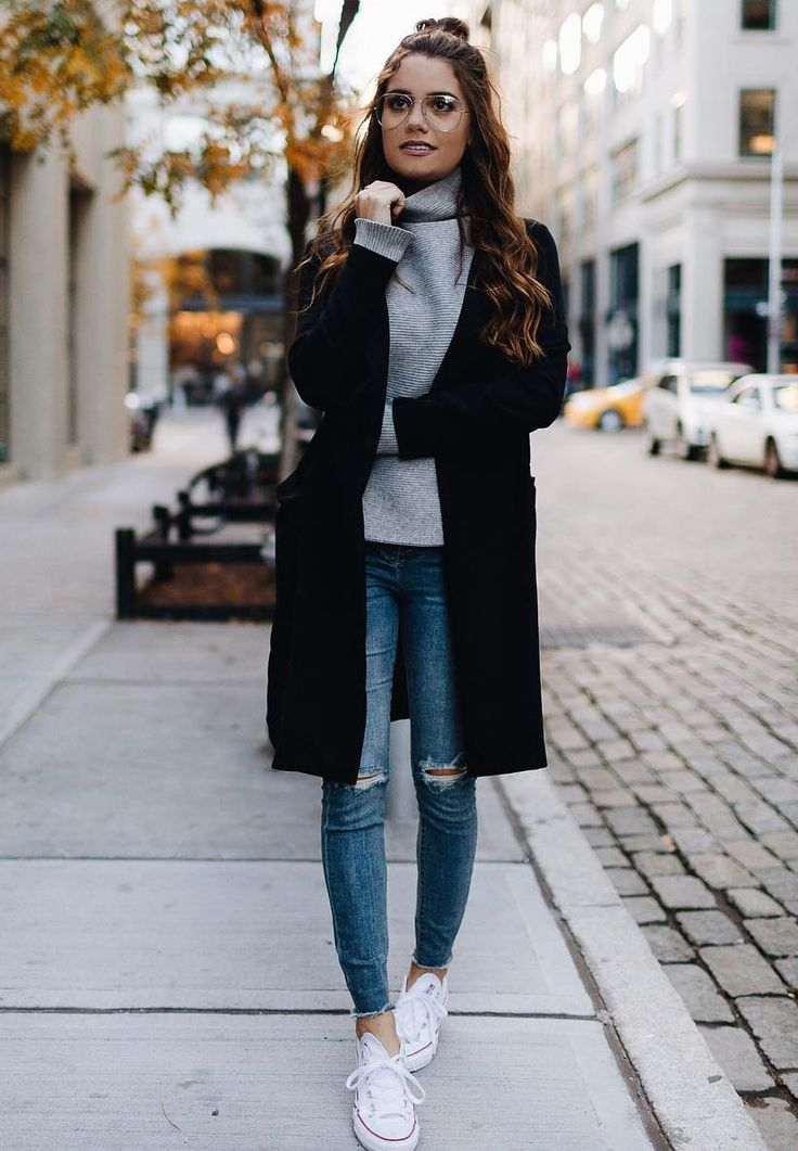 smiling in aviator glasses, concrete ribbed turtleneck, black overcoat, distressed denims, white sneakers