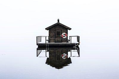 Johan Karlsson - Bastu. A photo of a floating sauna on a still ocean.
