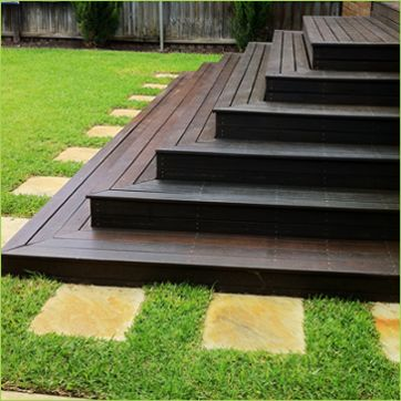 Beautiful dark decking ~ love the bordering with the stone as well