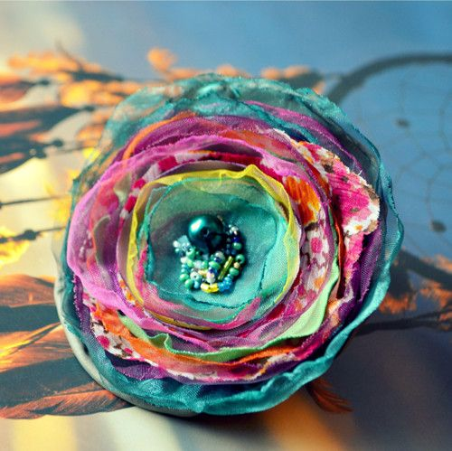 Máte ráda módní doplňky? Pak bohatá brož Zahradní víla je určena právě Vám. Originální brož je vyrobena z polyesteru a organzy.  Dozdobte si kabelku, sako, šál, večerní šaty či kabát. Skvěle se také hodí na mašli dárku nebo jako ozdoba na slavnostní stůl.  Rozměry: 10 cm (šířka), 2 cm výška  Zapínání: brožový můstek