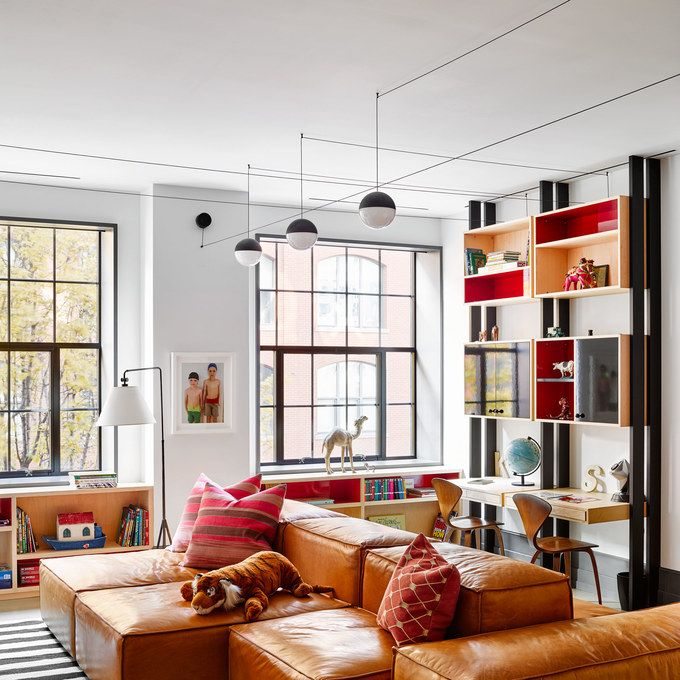 watts-schreiber-manhattan-loft-08.jpg Avoid growing pains. Watts and Schreiber's sons now relax, work, and horse around in a decidedly grown-up playroom, complete with a Living Divani leather sectional sofa, a custom-made John Robshaw rug, ceiling lights by Michael Anastassiades for Flos, and Norman Cherner chairs at the desks from Design Within Reach.