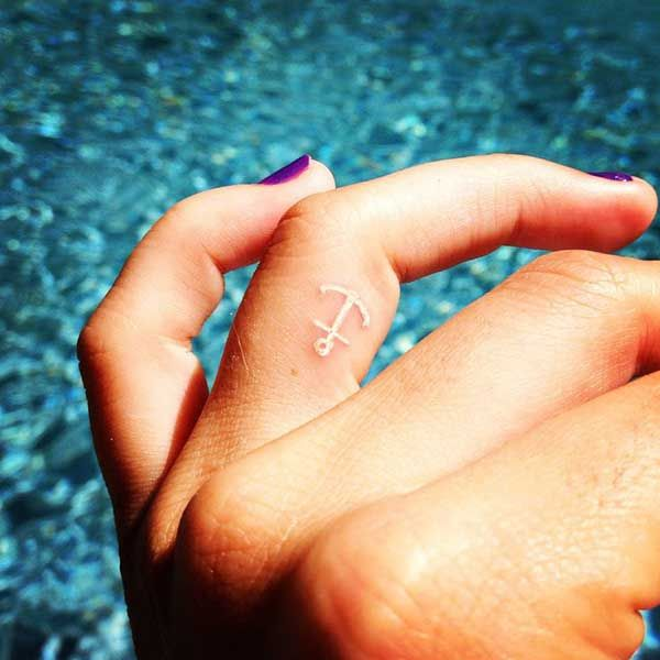 white ink anchor finger tattoo