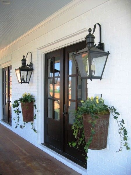 Handsome entry - black doors, large scale lanterns & pair of great baskets for plants