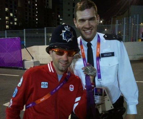 """Canadian men's eight coxswain Brian Price via Twitter @brianprice2012: """"Fun things to do with a medal #coolcop #london2012"""""""