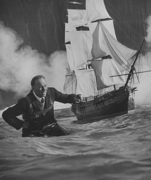 Special effects dir. John Fulton wading in tank w. large model of sailing ship, in a jacket and tie no less! Now that's a class act.  1956. Photo by Allan Grant