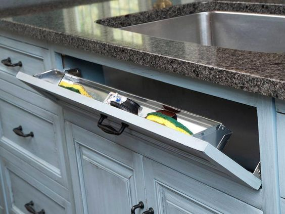 """To really maximize the storage in your kitchen, put unused areas to work. Typically, the """"drawer"""" in front of the kitchen sink is just a false front, but with the addition of cleverly hidden hinges and a stainless steel tray, it becomes out-of-sight storage for wet sponges and scrub brushes. Photo courtesy of Mullet Cabinets, Inc."""