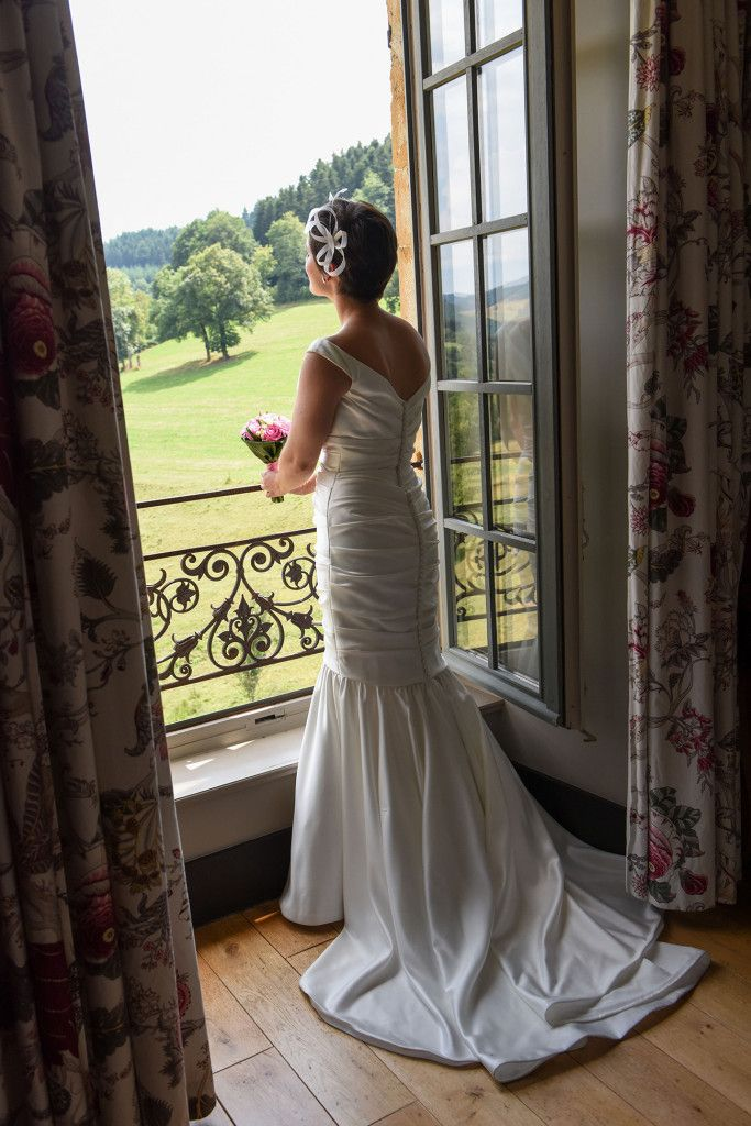 Bride looking through the window at Chateau (Castle) de Pranemoux in France. By Anais Phototgraphy.