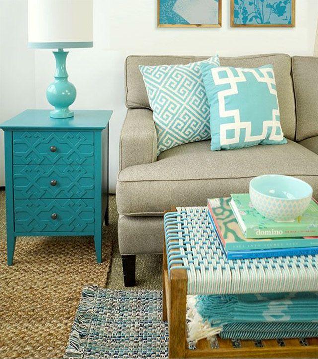 Sala de estar con sofá en color beige y cojines color turquesa con blanco, mesa de arrimo turquesa y alfombras color beige y turquesas