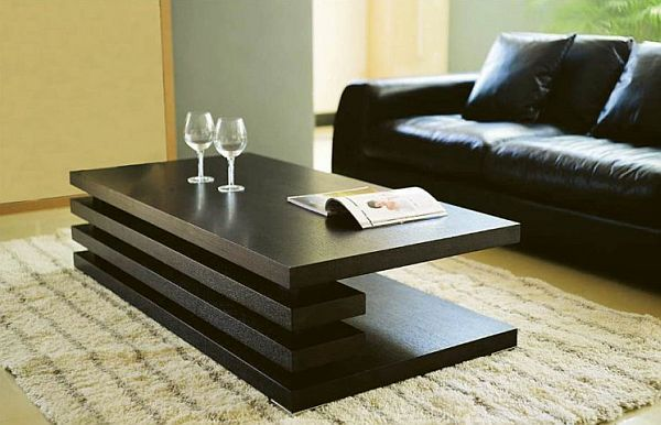 This particular coffee table is made of wood it has a simple design. It has no legs so it sits directly on the ground. It might be a little more difficult to move it around but that shouldn't be a big problem. It has a rectangular shape and the base and the top and held together by two smaller pieces placed parallel in between.