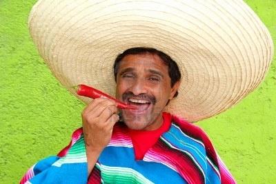Sombrero de poncho mexicano hombre comiendo hot rojo de ají México Foto de archivo