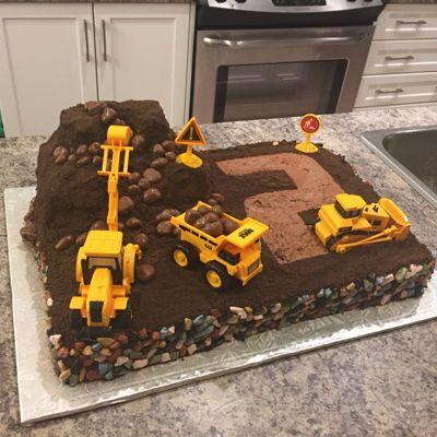 Digger Cake Dirt digger cake. Chocolate buttercream and chocolate cookie dirt. Chocolate rocks around the edging. Chocolate sponge boulders.