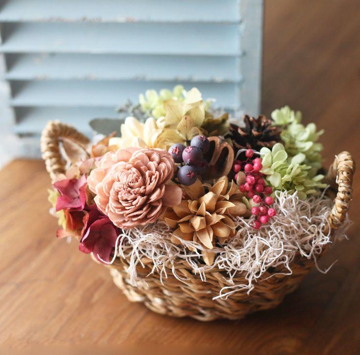 プリザーブドフラワー、木の実などをカゴにたっぷりアレンジしました。 色合いは落ち着いたアンティークカラーのお花をメインに 鮮やかなピンクのペッパーベリー、黄緑のアジサイを合わせることにより 華やかさもプラスしました。  玄関の飾りとして、テーブル飾りとしてもオススメです。 テーブルの中心に飾れるように裏面にもお花を入れています。  ラッピングしてお届けいたします。 お誕生日やご結婚、お引越しのお祝いとしてプレゼントにも。 メッセージカードご希望の方は4種類より選んでいただけます。