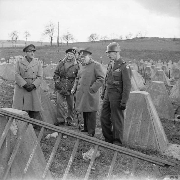 Winston Churchill with Field Marshal Sir Alan Brooke, Field Marshal Montgomery and General Simpson (Commanding 9th US Army) among 'dragons teeth' obstacles on the Siegfried Line near Aachen, 4 March 1945.