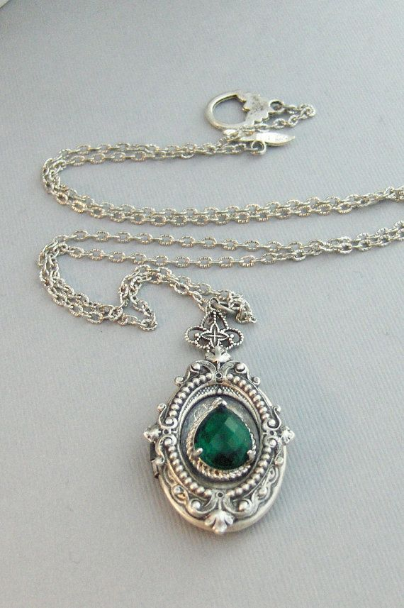 This antique silver locket has a beautiful Emerald adorned to the front of this silver oval locket. In the center sits a vintage emerald green