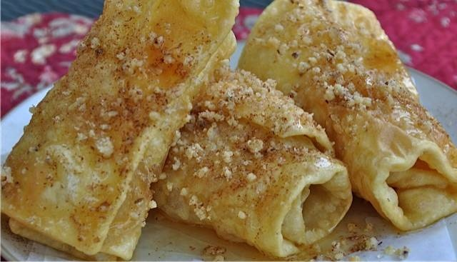 """Diples (THEE-ples) In case you are not familiar with them, Diples get their name from the Greek word for """"fold."""" They are thin sheets of dough that are folded while being fried into a crispy package that is then drizzled with honey and dusted with cinnamon and ground walnuts."""