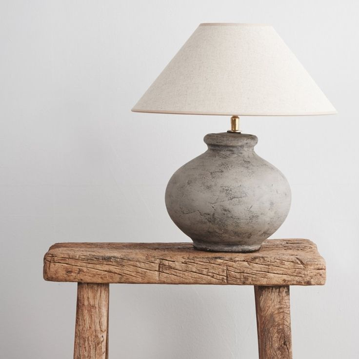 This table lamp features an unfinished ceramic base with an empire shade made of natural linen. Handmade in Belgium