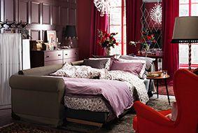 Rum med bäddsoffa från IKEA, bäddad som säng. Rumsavdelare mot väggen.