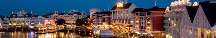 Disney's BoardWalk lights up in the early evening as its reflection bounces off of Crescent Lake