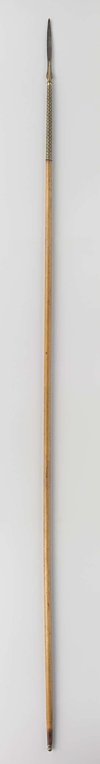 Anonymous | Lans van het wapenrek van Gouverneur-Generaal J.C. baron Baud, Anonymous, c. 1800 - c. 1900 | Ronde houten schacht met lange smalle kling, die bij de basis is verguld en met bladmotieven is versierd. De bovenzijde van de schacht heeft op het vergulde ijzeren omhulsel met gouddraad geweven ruitvormige motieven. Aan de onderzijde van de schacht zit een koperen balustervormige knop.