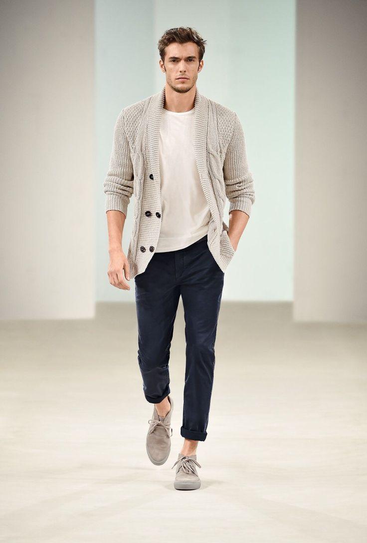 blusa branca lisa, cardigan bege, calça chino azul marinho com barra dobrada e desert boots bege.