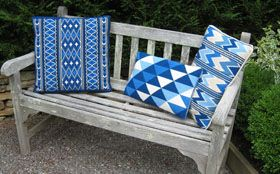 a group of blue and white pillows in the cross-point collection for stitching