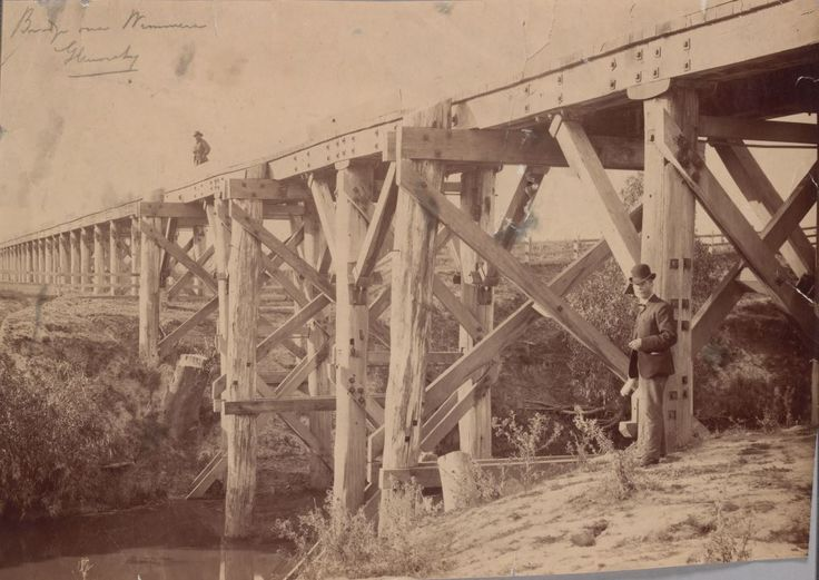 Wooden bridge over the Wimmera River at Glenorchy, c1880. A man with hat stands on bridge and another on bank in foreground. SLV