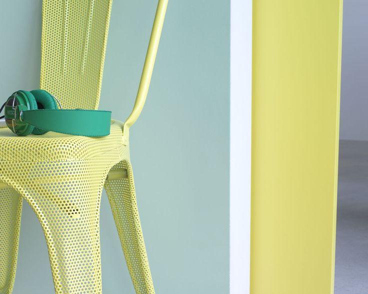 Illuminez votre intérieur avec des couleurs printanières. La porte et la chaise jaune citron apportent une touche de gaieté à cette entrée vert pâle au sol gris froid très contemporain.
