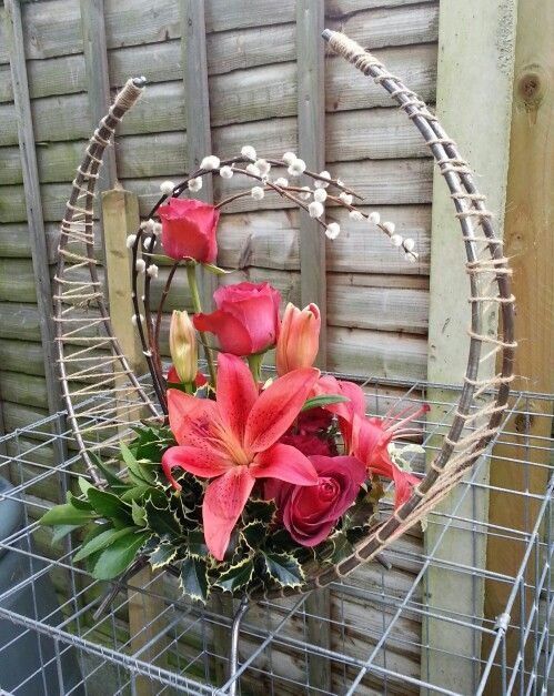 Red roses and Lilies sitting on a Holly and Ruscus base with Salix complimenting the arc of the stand.***R***